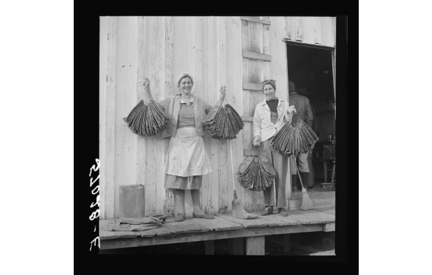 Spanish trapper's wife and sister-in-law holding dried muskrat skins in front of their camp